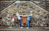 Hip couple dancing by wall with bikes — Stock Photo