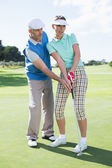 Man coaching his partner on the putting green — Foto de Stock
