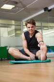 Fit man warming up in fitness studio — Zdjęcie stockowe