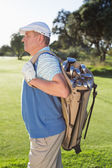 Golfer standing holding his golf bag — Stockfoto