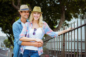 Hip couple smiling by railings — Stock Photo