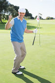 Golfer cheering on putting green — Stock Photo