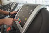 Man adjusting settings on treadmill — Stock Photo