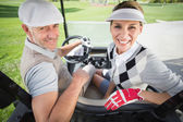 Golfing couple in golf buggy — Stock Photo