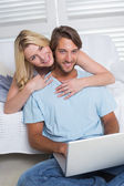 Couple on couch using laptop — Foto de Stock
