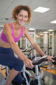 Fit woman on the spin bike smiling — Stock Photo