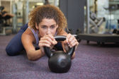 Fit woman lying with kettlebell — Stock fotografie