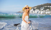 Blonde in sundress with her bike at beach — Stockfoto