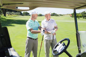 Golfing friends beside buggy — Stock Photo