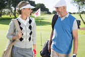 Golfing couple walking away from eighteenth hole — Stockfoto
