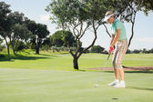 Female golfer putting her ball — Stok fotoğraf