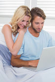 Couple on couch using laptop — 图库照片