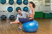 Trainer watching his client using exercise ball — Photo