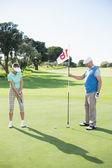 Golfing couple at the eighteenth hole — Stock Photo