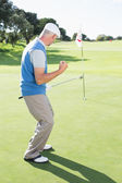 Happy golfer cheering on putting green — Stock Photo
