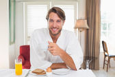 Man having breakfast in bathrobe — Stock Photo
