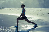 Fit woman doing lunges on beach — 图库照片