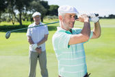 Golfer swinging his club with friend — Stockfoto