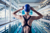 Fit swimmer standing by the pool — Stock fotografie