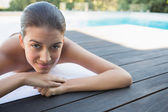 Smiling brunette lying on a towel poolside — Photo