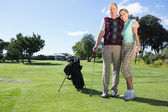 Golfing couple standing smiling at camera — Stock Photo