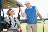 Golfing couple on buggy — Stock Photo