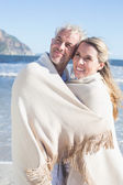 Couple wrapped up in blanket on the beach — Stok fotoğraf