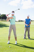 Golfing couple teeing off for the day — Stock Photo