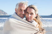 Couple wrapped up in blanket on the beach — ストック写真