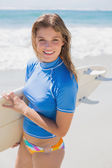 Surfer girl on beach with surfboard — Stock Photo