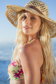 Blonde in straw hat and bikini on beach — Photo