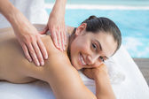 Brunette getting a massage poolside — Stock Photo