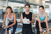 Fit women in a spin class with trainer — Stock Photo
