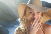 Blonde in straw hat on beach — Stockfoto