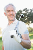 Smiling handsome golfer looking away — Stock Photo
