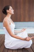 Brunette in white sitting in lotus pose — Stock Photo