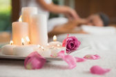 Candles and rose petals on massage table — Stock Photo