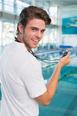 Swimming coach by the pool looking at stopwatch — Stock Photo
