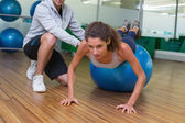 Trainer helping his client doing push up — Stock Photo