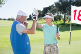 Golfing couple high fivin at eighteenth hole — Stock Photo
