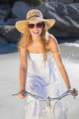 Blonde in sundress on bike at the beach — Stock Photo