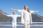 Couple with arms outstretched at the beach — Stockfoto