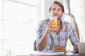 Man drinking orange juice at breakfast — Stock Photo