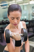 Fit brunette lifting heavy dumbbell — Stock Photo