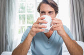 Man on bed drinking coffee — Stock Photo
