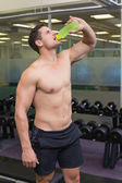 Bodybuilder drinking sports drink — Stock Photo
