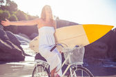 Surfer in sundress on bike holding surfboard — Stock fotografie