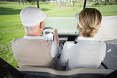 Golfing couple driving in golf buggy — Stock Photo