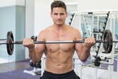 Bodybuilder lifting barbell weight — Stock Photo