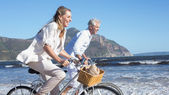 Couple riding their bikes on the beach — Stock Photo